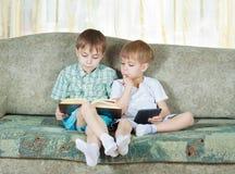 Dois meninos de leitura. Com o livro de papel e eletrônico Fotos de Stock Royalty Free