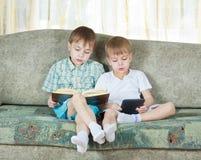 Dois meninos de leitura. Com o livro de papel e eletrônico Imagens de Stock Royalty Free