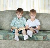 Dois meninos de leitura. Com o livro de papel e eletrônico Imagens de Stock