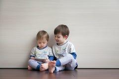 Dois meninos de vista bonitos olham uns desenhos animados foto de stock