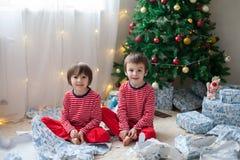 Dois meninos doces, abrindo apresentam no dia de Natal Fotos de Stock Royalty Free