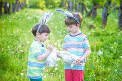 Dois meninos e amigos das crianças nas orelhas do coelhinho da Páscoa durante o tra Imagem de Stock Royalty Free