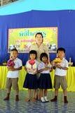 Dois meninos e duas meninas estão guardando a bandeja do suporte da decoração fotografia de stock royalty free