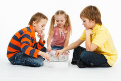 Dois meninos e menina bonita que jogam a xadrez imagens de stock