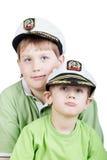Dois meninos em t-shirt verdes e em pico-tampões do mar branco Imagens de Stock