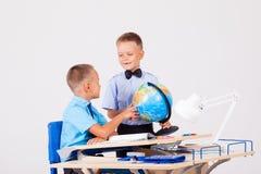 Dois meninos estão aprendendo o globo para a mesa na escola foto de stock
