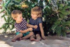 Dois meninos estão comemorando o Natal na praia Imagem de Stock