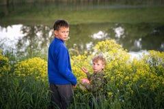 Dois meninos estão estando pela água imagem de stock royalty free