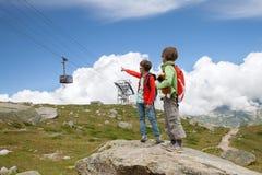 Dois meninos estão olhando o teleférico nas montanhas Imagem de Stock Royalty Free