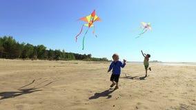 Dois meninos felizes que correm com os papagaios na praia video estoque