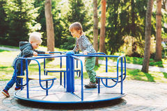 Dois meninos felizes que jogam no campo de jogos em um parque Fotos de Stock Royalty Free