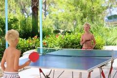 Dois meninos felizes que jogam o pong do sibilo fora Fotografia de Stock Royalty Free