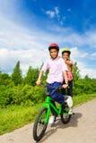 Dois meninos felizes que montam mesmos bike ambos que estão Fotografia de Stock Royalty Free