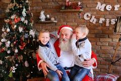 Dois meninos gêmeos fazem alternadamente o desejo na orelha de Santa Claus no de Fotografia de Stock