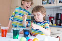 Dois meninos louros pequenos da criança que colorem ovos para o feriado da Páscoa Imagem de Stock Royalty Free