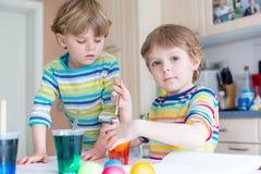 Dois meninos louros pequenos da criança que colorem ovos para a Páscoa Fotografia de Stock