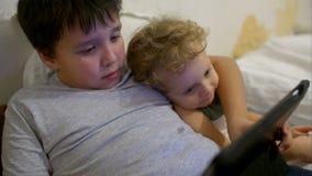 Dois meninos na cama com almofada de toque Um jogo de jogo video estoque