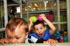 Dois meninos no campo de jogos interno fotografia de stock royalty free