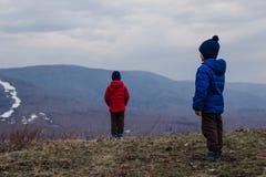 Dois meninos nos revestimentos e nos chapéus estão na montanha e no olhar na distância em um dia frio nevoento na mola adiantada imagem de stock