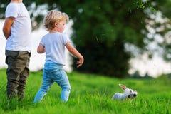 Dois meninos novos com um cão pequeno jogam exterior Foto de Stock Royalty Free