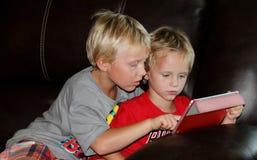 Dois meninos novos que olham uma tabuleta Fotos de Stock Royalty Free