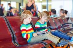 Dois meninos pequenos cansados do irmão no aeroporto Fotografia de Stock Royalty Free