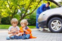 Dois meninos pequenos do irmão na segurança alaranjada investem durante seu fathe Fotos de Stock