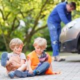 Dois meninos pequenos do irmão na segurança alaranjada investem durante seu fathe Imagem de Stock Royalty Free