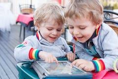 Dois meninos pequenos do irmão que têm o divertimento junto com o PC da tabuleta Imagens de Stock