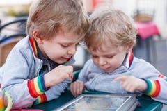 Dois meninos pequenos do irmão que têm o divertimento junto com o PC da tabuleta Fotografia de Stock Royalty Free