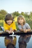 Dois meninos permitiram os barcos de papel do cais do rio Fotos de Stock Royalty Free