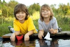 Dois meninos permitiram os barcos de papel do cais do rio Imagem de Stock