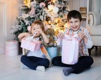 Dois meninos perto de uma árvore de abeto que desembala presentes imagem de stock royalty free