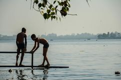 Dois meninos pobres desconhecidos não identificados do precário, short vestindo, jogando perto da praia de Versova, Mumbai, Mahar imagem de stock royalty free