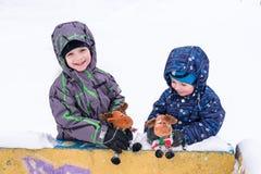 Dois meninos prées-escolar adoráveis do irmão de crianças no desgaste do inverno sentam o amou Foto de Stock Royalty Free