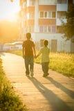 Dois meninos que correm junto na rua Imagens de Stock Royalty Free