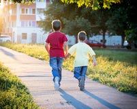 Dois meninos que correm junto na rua Fotos de Stock Royalty Free