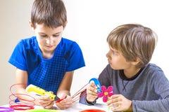 Dois meninos que criam com a pena da impressão 3d Imagens de Stock