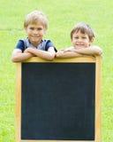 Dois meninos que estão no quadro-negro exterior Fundo verde imagens de stock royalty free