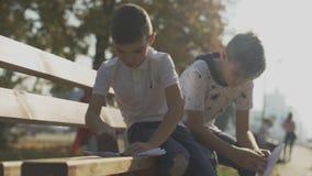 Dois meninos que fazem os planos de papel fora Crianças que sentam-se no banco no parque video estoque