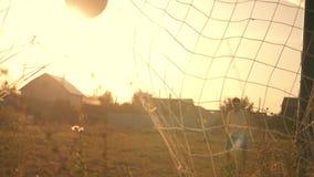 Dois meninos que jogam o futebol no por do sol Uma bola de futebol está batendo Objetivo do futebol Sonhos do ` s das crianças da filme