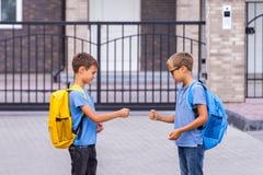 Dois meninos que jogam o jogo de papel das tesouras da rocha após a escola fotos de stock royalty free