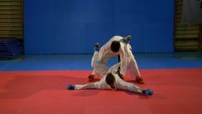 Dois meninos que lutam no combate e em um colocaram o outro com técnicas das artes marciais vídeos de arquivo