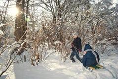 Dois meninos que montam no trenó no inverno Imagem de Stock