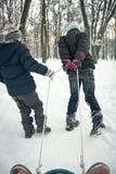 Dois meninos que montam no trenó no inverno Fotografia de Stock Royalty Free