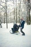 Dois meninos que montam no trenó no inverno Imagens de Stock