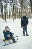Dois meninos que montam no trenó no inverno Fotos de Stock