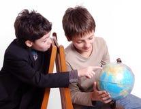 Dois meninos que pesquisam a esfera isolada no branco fotografia de stock royalty free
