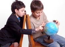 Dois meninos que pesquisam o globo isolado no branco fotos de stock royalty free