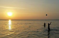 Dois meninos que plaing a bola no mar Imagem de Stock